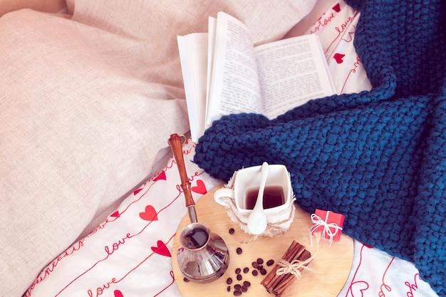 Frühstück im bett mit kaffee und buch in isolationszeit