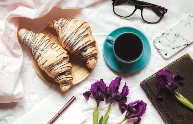 Frühstück im bett. morgen, croissant, kaffee, blumen und ein notizbuch mit einem stift. planung
