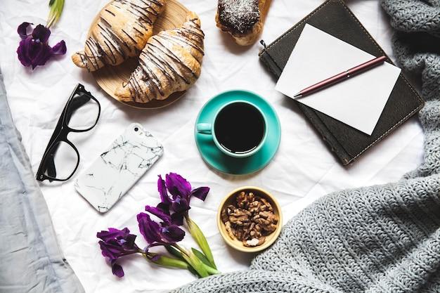 Frühstück im bett. morgen, croissant, kaffee, blumen und ein notizbuch mit einem stift.