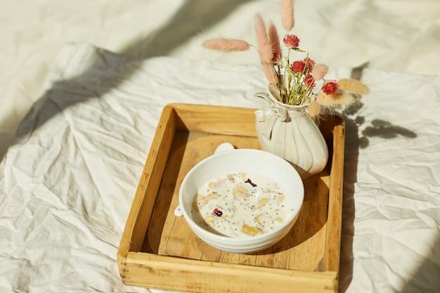 Frühstück im bett, probieren sie es mit schüsselmüsli, müsli und blume im sonnenlicht zu hause, zimmermädchen bringt tablett mit frühstück ins hotelzimmer, guter service