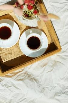Frühstück im bett, probieren sie es mit zwei tassen kaffee und blumen im sonnenlicht zu hause, zimmermädchen bringt tablett mit frühstück im hotelzimmer, guter service