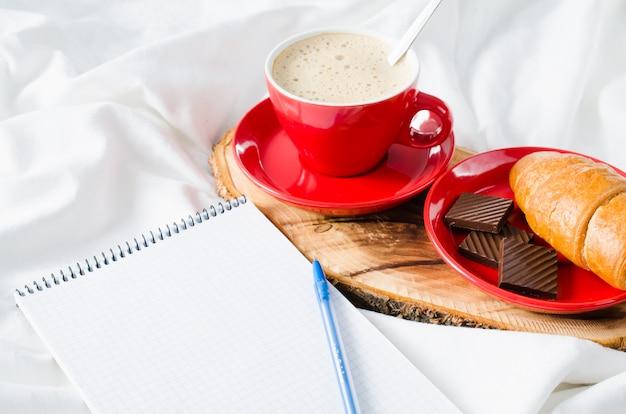 Frühstück im bett und leeres notizbuch für anmerkung.