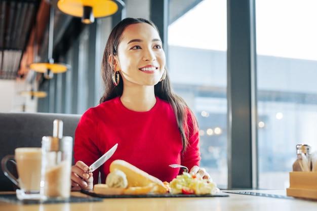 Frühstück im café. nahaufnahme einer strahlenden, ansprechenden frau mit rotem pullover, die im café frühstückt?
