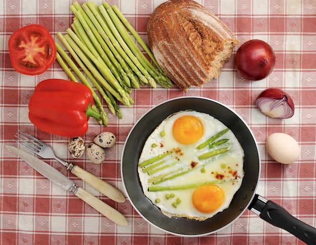 Frühstück im dörflichen stil - spiegeleier in einer pfanne mit spargel und zwiebeln