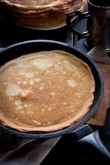 Frühstück im rustikalen stil: viele frisch gekochte crepes oder pfannkuchen, oben mit marmelade gewässert und mit beeren dekoriert. vor dem hintergrund panand eine pfanne.