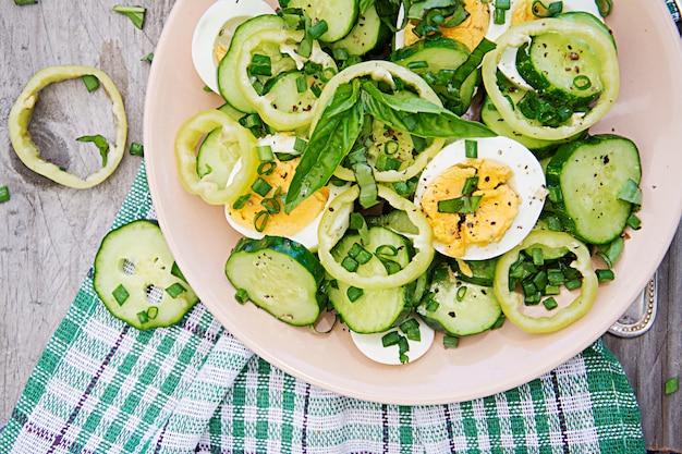 Frühstück im sommergarten. salat von eiern und gurken mit frühlingszwiebeln und basilikum. ansicht von oben. flach liegen