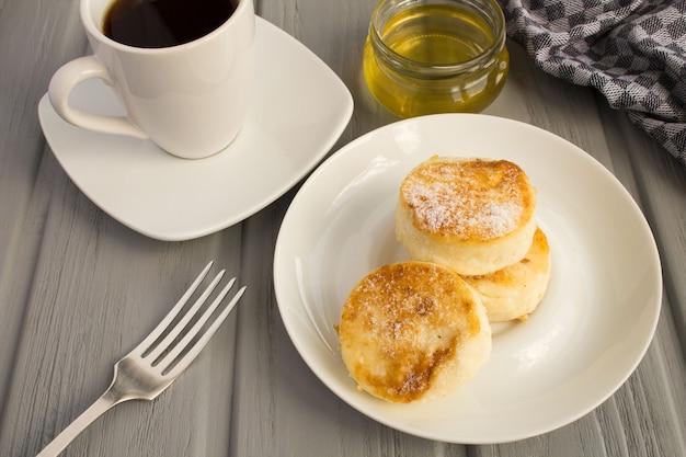 Frühstück: käsepfannkuchen, kaffee und honig auf grauem holzhintergrund
