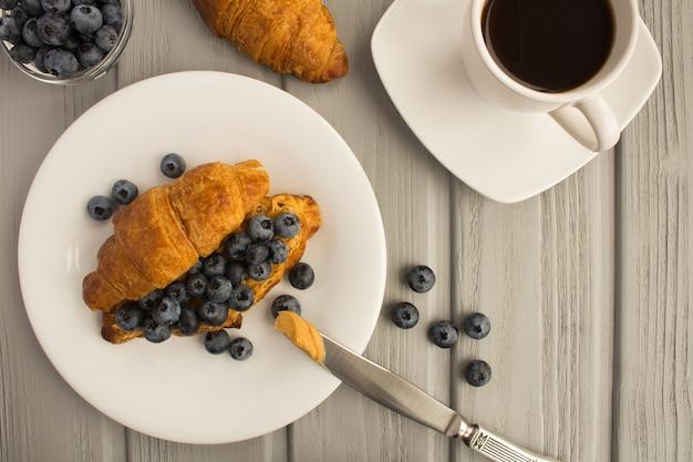 Frühstück: kaffee, croissant mit erdnusspaste und blaubeeren auf dem grauen hölzernen hintergrund. draufsicht. kopierraum.