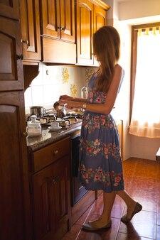 Frühstück - mädchen in der küche gießt kaffee in eine tasse aus der kaffeekanne
