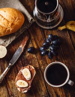Frühstück mit bananensandwich mit schokoladenaufstrich, kaffeetasse und trauben. vertikale ausrichtung und ansicht von oben.