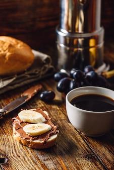 Frühstück mit bananensandwich mit schokoladenaufstrich, kaffeetasse und trauben