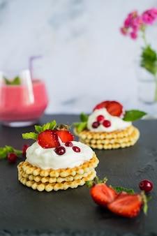 Frühstück mit bio-smoothie und köstlichen belgischen waffeln mit schlagsahne und erdbeeren