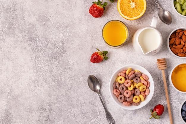 Frühstück mit bunten müsliringen, obst, milch, saft