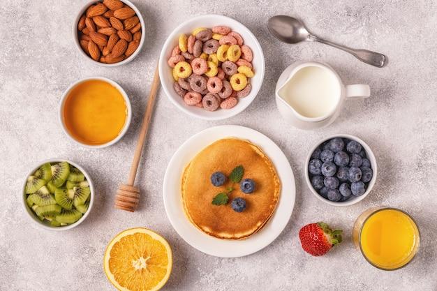Frühstück mit bunten müsliringen, pfannkuchen, obst, milch, saft