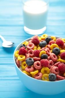 Frühstück mit corn flakes, milch und beeren auf blauem hintergrund. ansicht von oben. vertikales foto