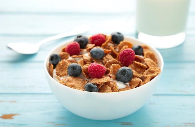 Frühstück mit corn flakes, milch und beeren auf blauem hintergrund. ansicht von oben