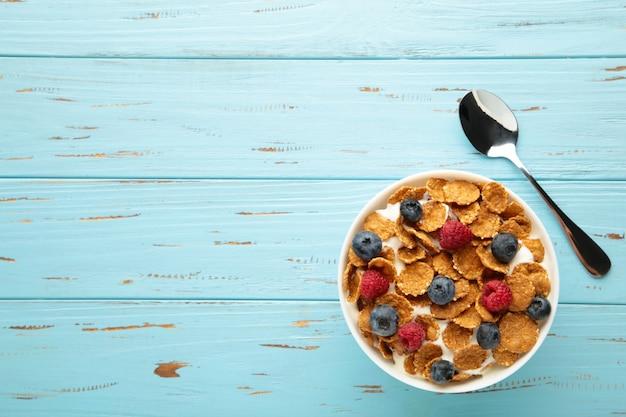 Frühstück mit corn flakes, milch und beeren auf blauem hintergrund. vertikales foto