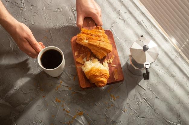 Frühstück mit croissant auf schneidebrett und schwarzem kaffee