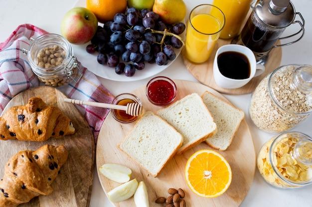 Frühstück mit croissant. orangensaft in einer glasflasche.