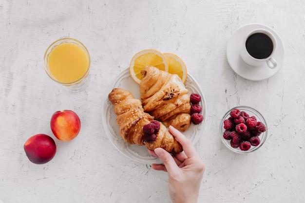 Frühstück mit croissants, einer tasse kaffee, himbeeren und orangensaft von oben
