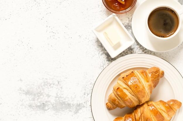 Frühstück mit croissants. frische knusprige croissants und kaffee, ansicht von oben.