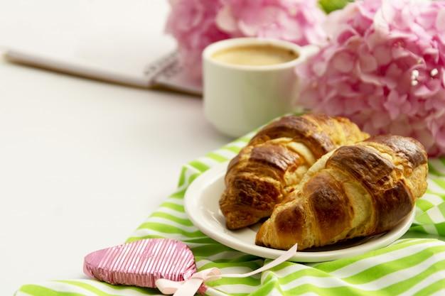 Frühstück mit croissants, rosa rosenblüte und kaffee