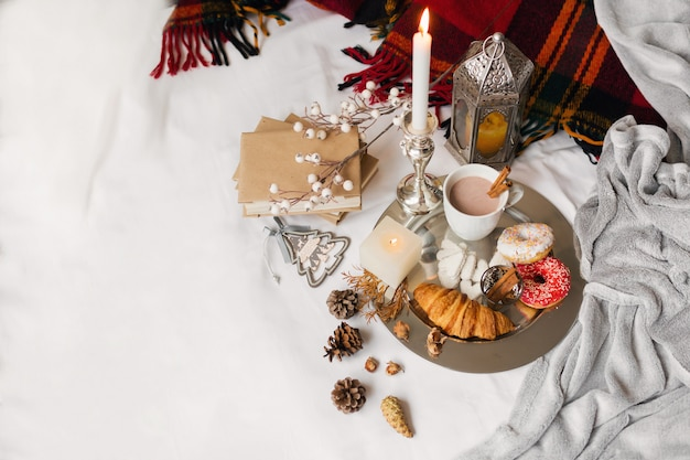 Frühstück mit donuts, croissants, keksen und teetasse auf einem tablett im bett