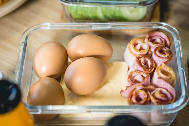 Frühstück mit eiern, käse und speck auf dem esstisch