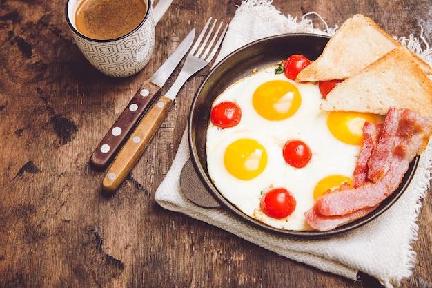 Frühstück mit eiern, kirschtomaten, speck und frisch geröstetem toast