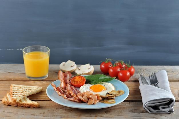 Frühstück mit eiern mit speck, bohnen, champignons, tomaten und spinat