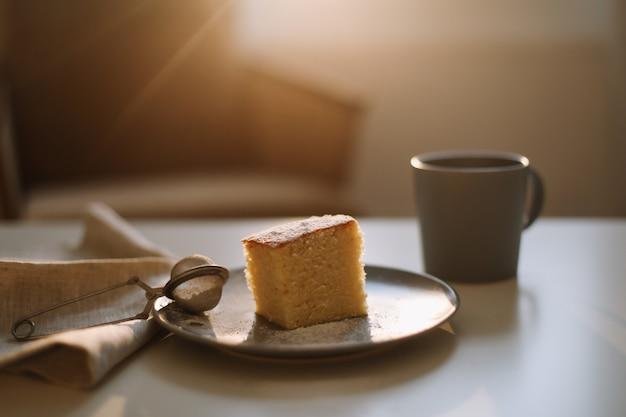 Frühstück mit einem stück hausgemachtem kuchen auf einem teller und einer tasse kaffee