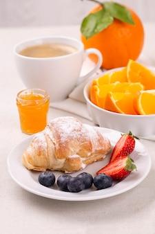 Frühstück mit einer tasse kaffee, frischem croissant, erdbeeren und blaubeeren und saftigen orangen