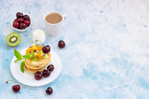 Frühstück mit einer tasse kaffee und einem stapel pfannkuchen, serviert mit schwarzkirsche, aprikose, kiwi und minze