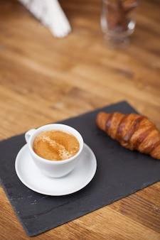 Frühstück mit espressotasse heißem kaffee und croissant auf einer schwarzen steinplatte. kaffee-aroma.