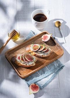 Frühstück mit feigen-, käse- und honigsandwich auf einem holzbrett und einer tasse kaffee auf weißem tisch, sonniger morgen