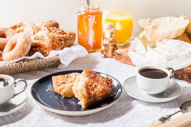 Frühstück mit französischem gebäck, brot, käse und kaffee