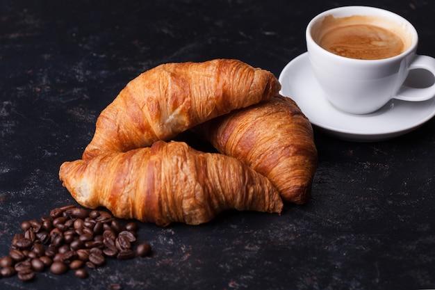 Frühstück mit frisch gebackenen croissants und tasse kaffee. goldene kruste.