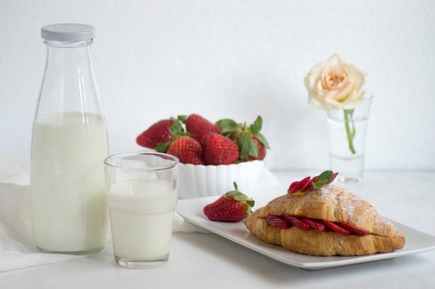 Frühstück mit frischem milchcroissant und erdbeeren und einer rose auf einem glas