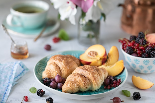 Frühstück mit frischen beeren und früchten mit croissants, tees und einem strauß sommerblumen.