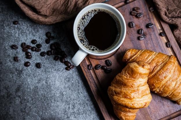 Frühstück mit frischen croissants und einer tasse schwarzen kaffees auf holzbrett
