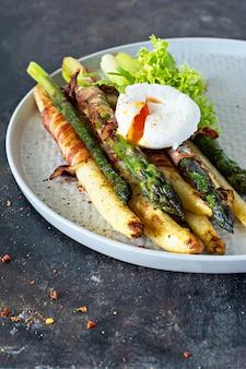 Frühstück mit gebackenem spargel in gewürzen mit speck, pochiertem ei
