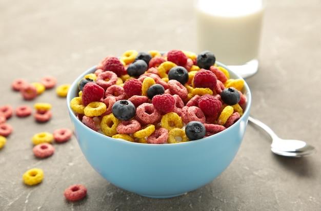 Frühstück mit getreide, milch und beeren auf grauem hintergrund. ansicht von oben. vertikales foto