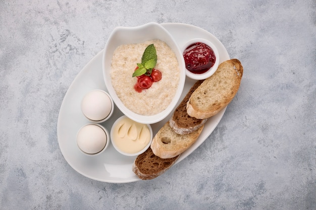 Frühstück mit haferbrei, butter, gekochten eiern, marmelade und toast, croutons, auf einer weißen oberfläche