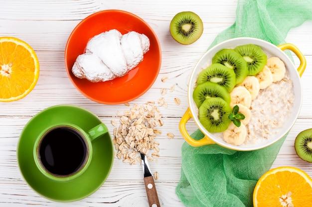 Frühstück mit haferbrei, croissant, obst und kaffeetasse.