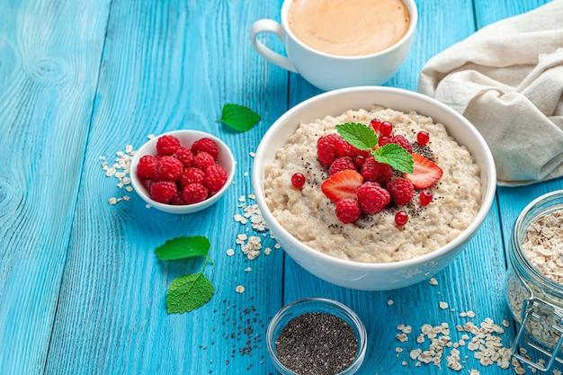 Frühstück mit haferflocken frische saftige beeren und chiasamen auf blauem hintergrund