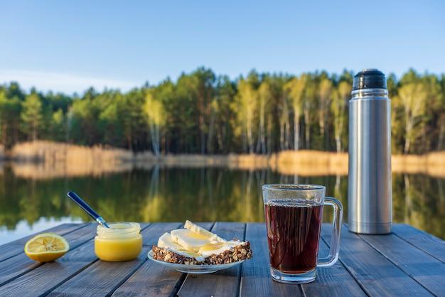 Frühstück mit heißem tee, käsesandwich und honig auf holztisch morgens neben dem see und wald im frühling, nahaufnahme. natur- und ernährungskonzept