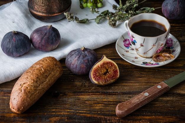 Frühstück mit kaffee, brot und ein paar feigen.
