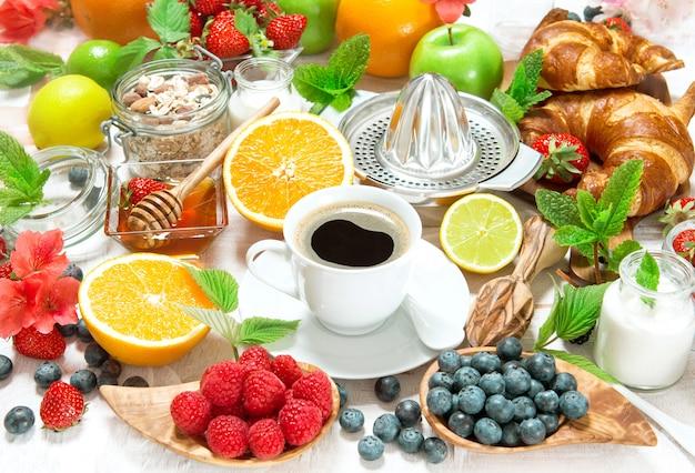 Frühstück mit kaffee, croissants und früchten. gesundes essen