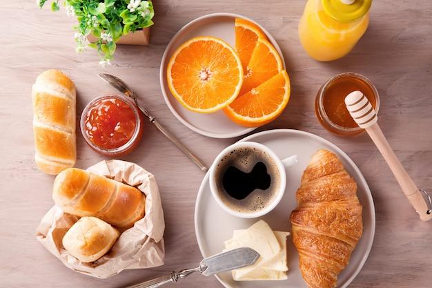 Frühstück mit kaffee, orangensaft und hörnchen. draufsicht
