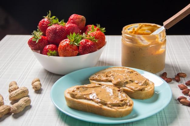 Frühstück mit kaffee und sandwiches mit erdnusspaste und erdbeeren